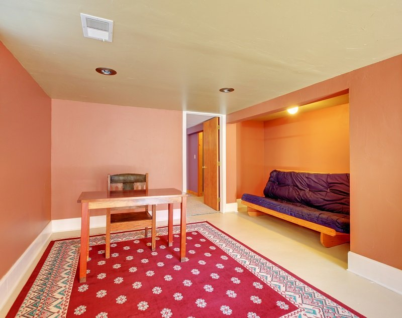 Large basement room with red rug and orange walls