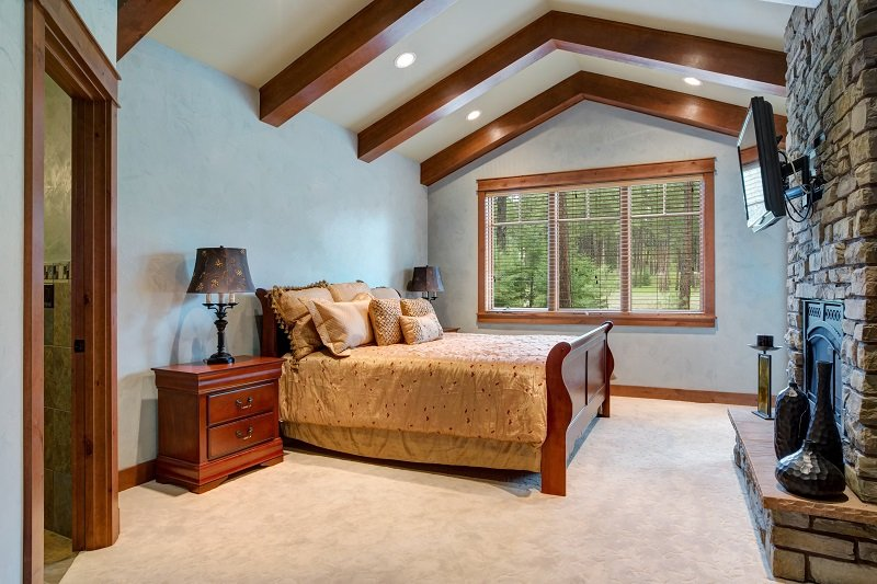 Chic master bedroom: vaulted ceiling with wooden beams over the wood sleigh bed facing stone wall fireplace.