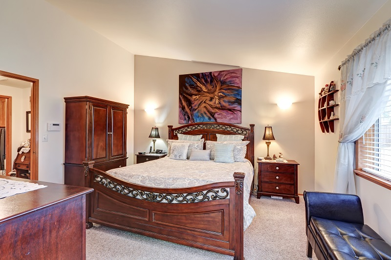 elegant master bedroom with wooden furniture and artwork