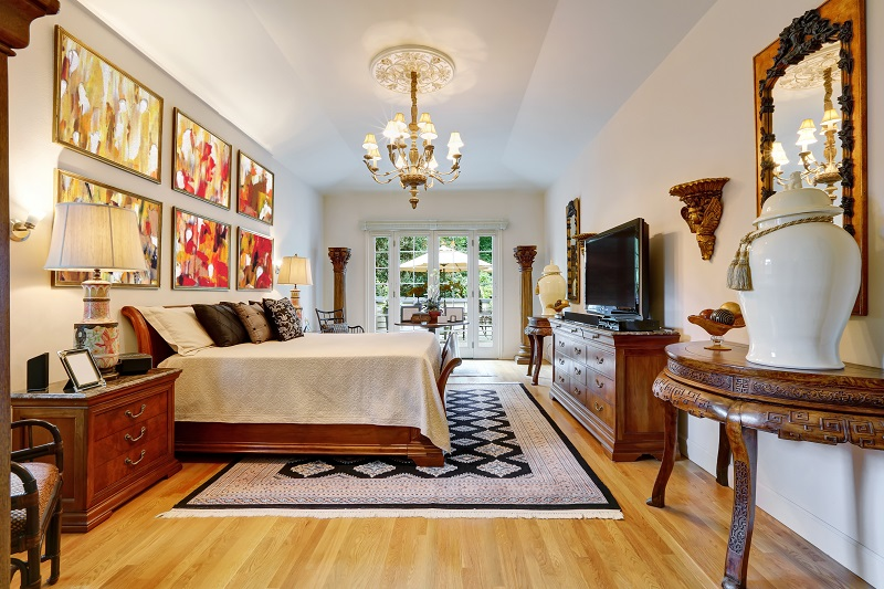 Luxury large master bedroom interior with antique carved wooden furniture, king size bed, vintage chandelier and hardwood floor.