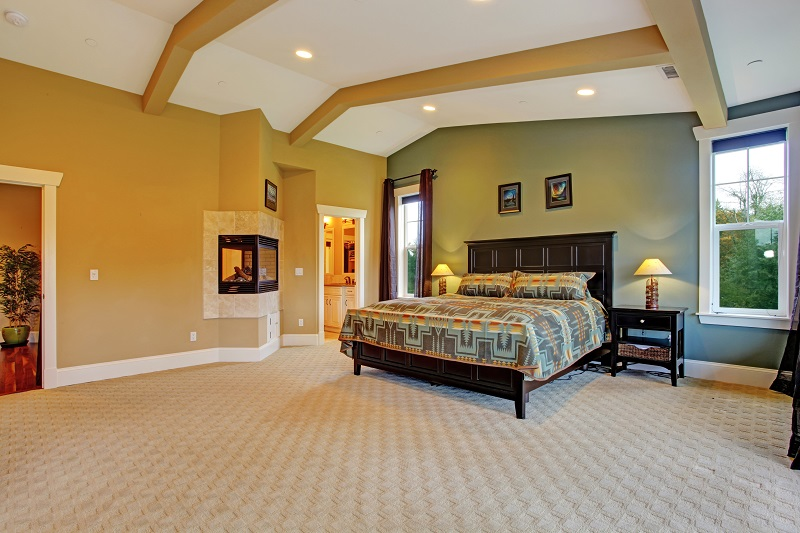 Spacious master bedroom with high coffered ceiling, beige carpet floor and fireplace built in the wall