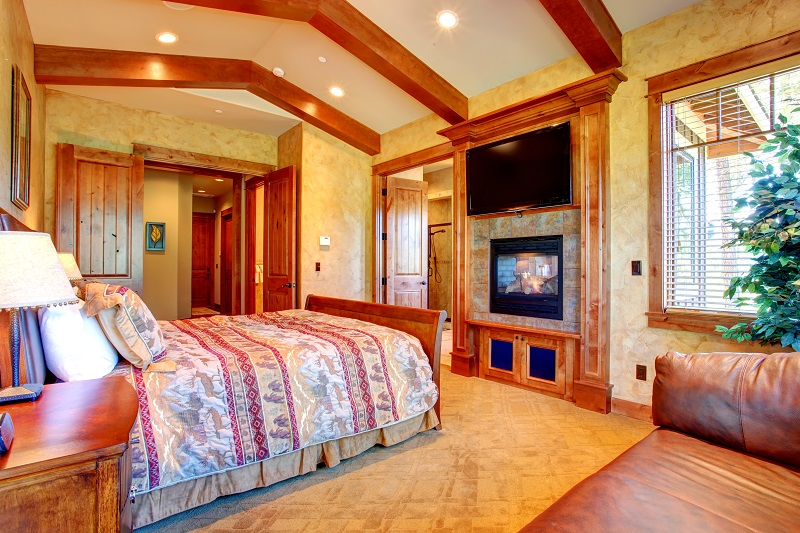 Beautiful gold bedroom with ceiling beams and fireplace.
