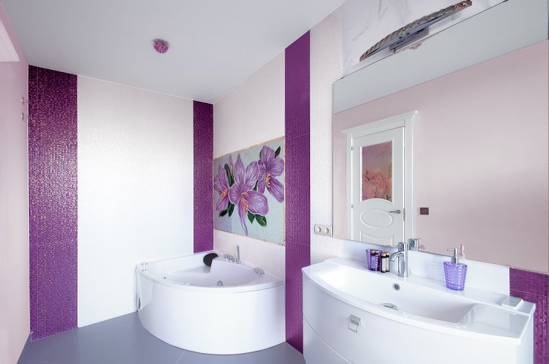 Modern Bathroom interior with a mosaic panel. White bathtub against violet and white wall