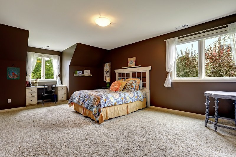 Spacious master bedroom interior with soft carpet floor and dark brown walls. Room has small office area by the window