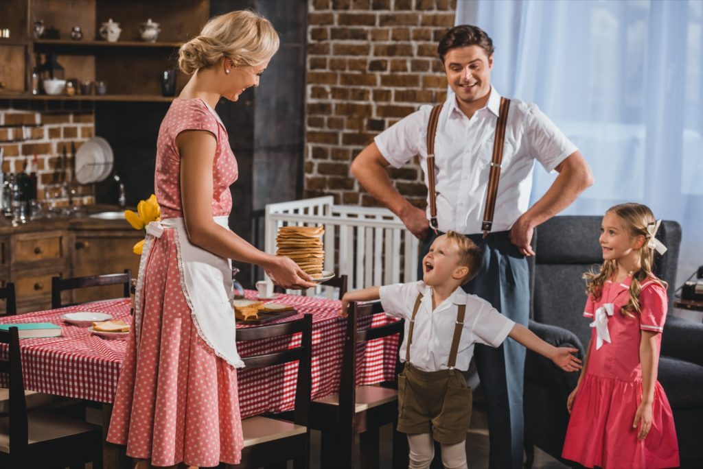 1950s style family having pancakes for breakfast where woman and daughter is wearing pink dresses