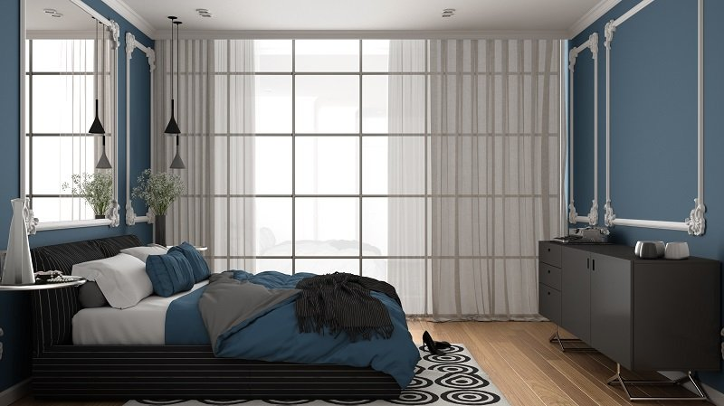 Modern blue colored bedroom in classic room with wall moldings, parquet, double bed with duvet and pillows, minimalist bedside tables, mirror and decors.