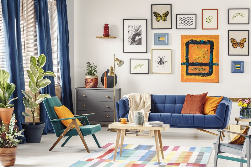 modern living room color combinations - Simple posters hanging on the wall in bright living room interior with blue curtains, coffee table placed on colorful carpet, green armchair and navy couch