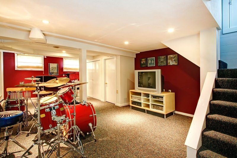 White basement room with red and burgundy walls, carpet floor. Rehearsal room with drums