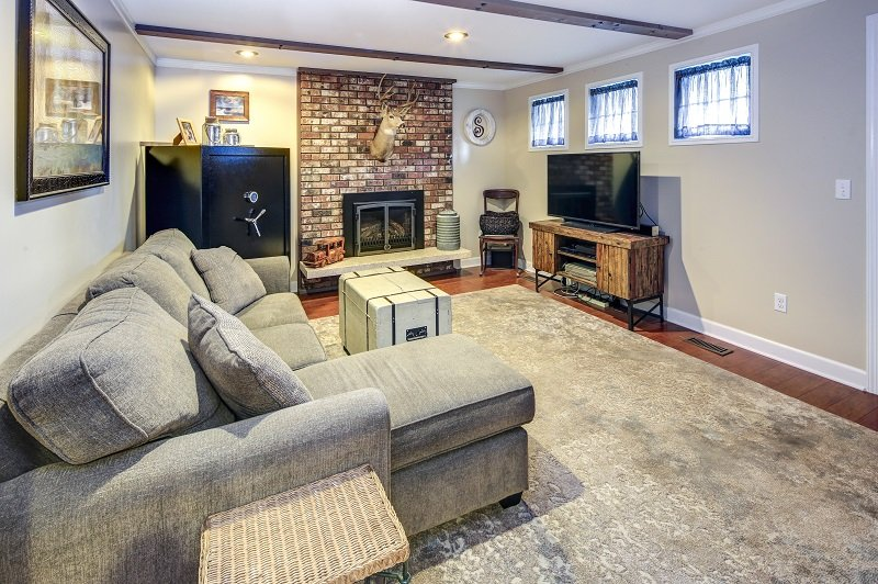 Basement living room space with fireplace and brick wall.