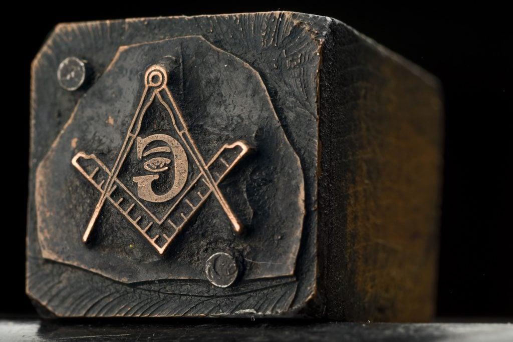 Freemasonry symbol on a slightly burnt wooden post