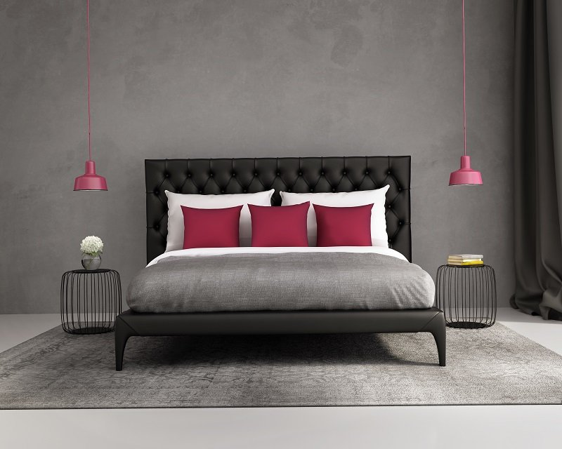 Grey wall and grey bed with red pillows
