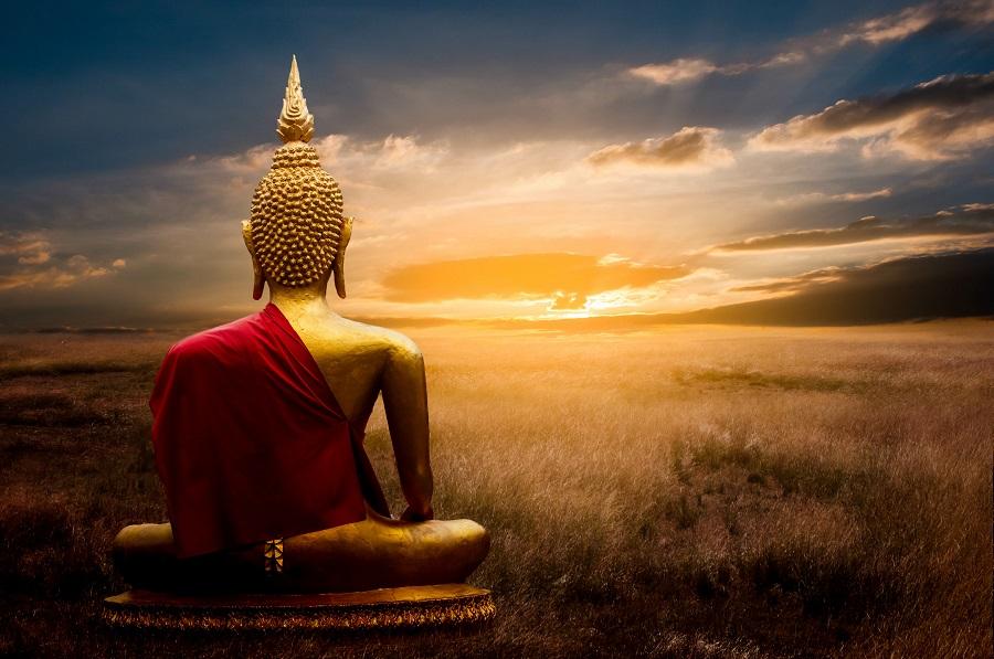 Buddha statue on field at sundown in Thailand