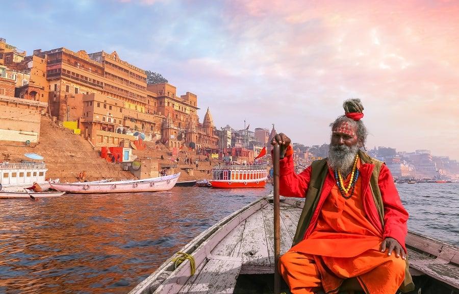 Indian Sadhu baba in orange clothes taking a boat ride on river Ganges