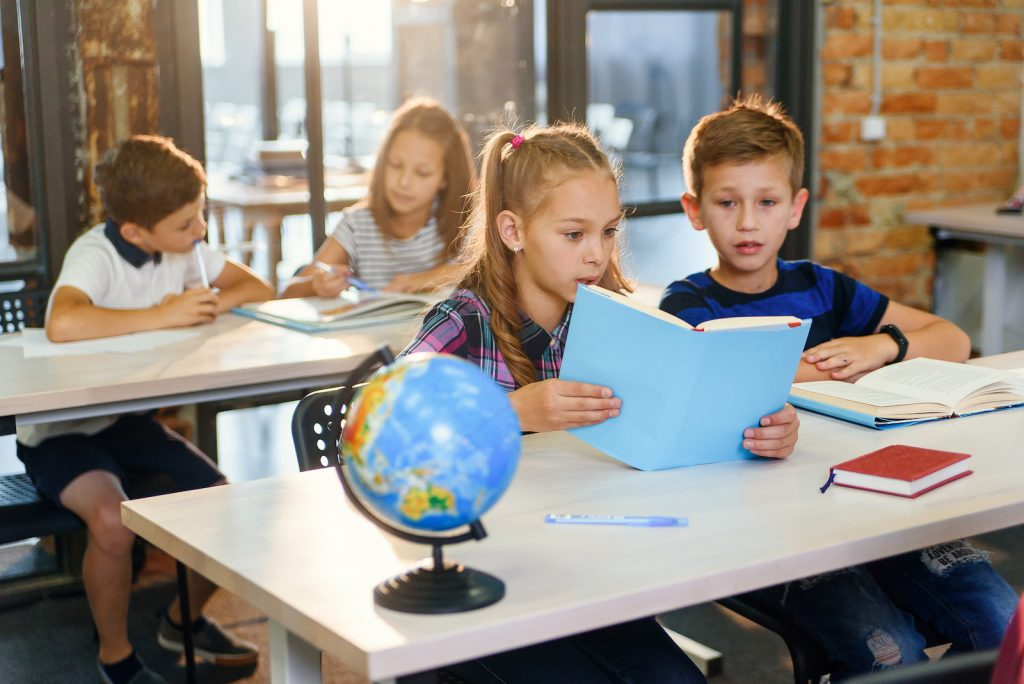 Kids reading books in history class