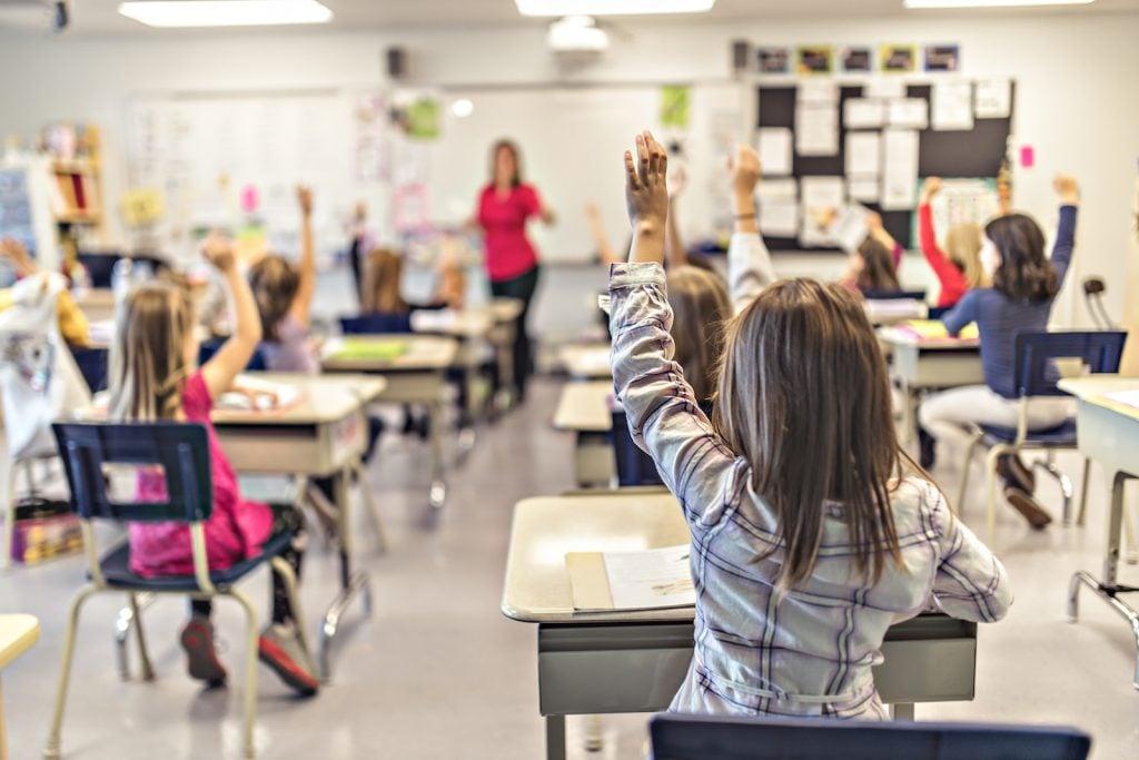 Kids raising hands in class at school