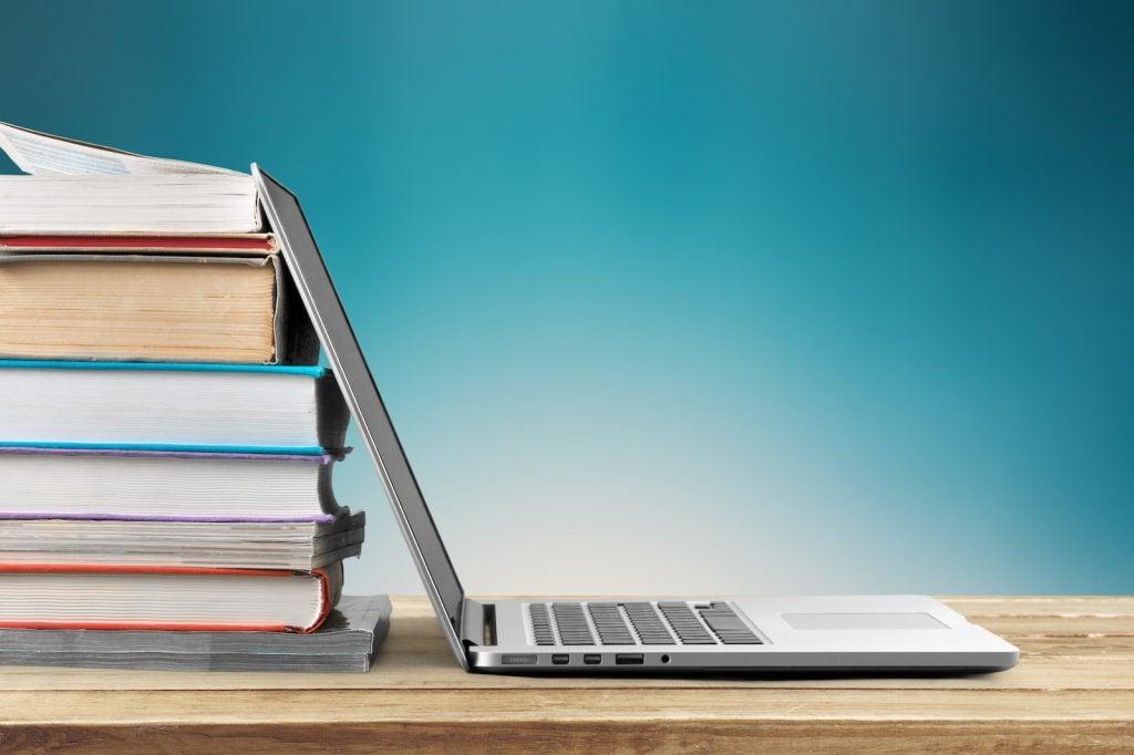 Laptop next to pile of school books
