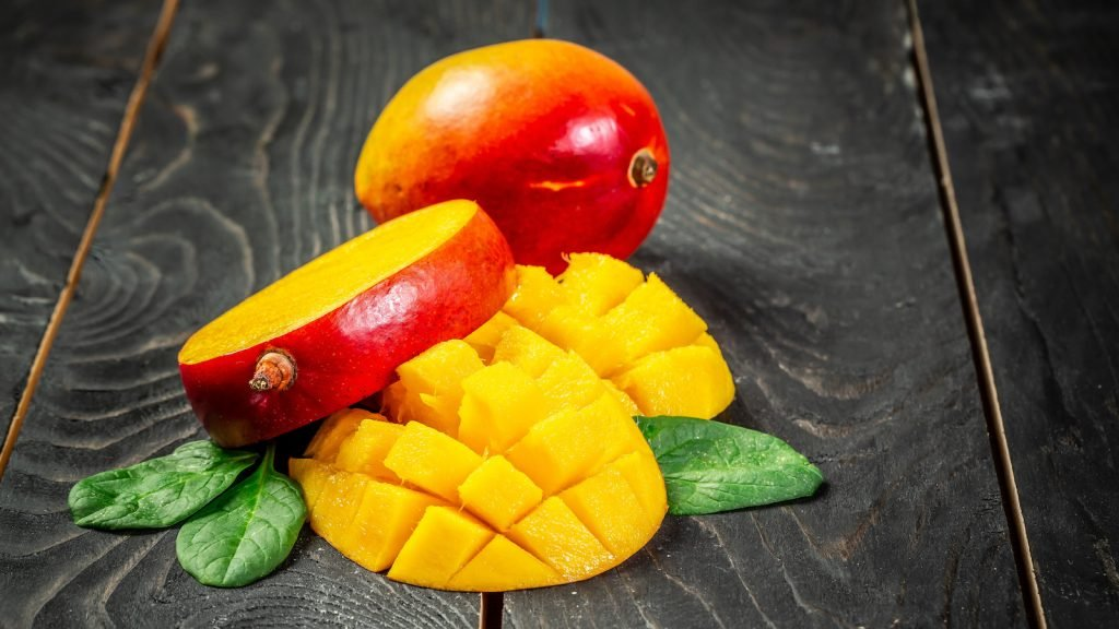 Fresh and beautiful whole mango fruit with another one sliced and diced mango chunks on a black wooden background
