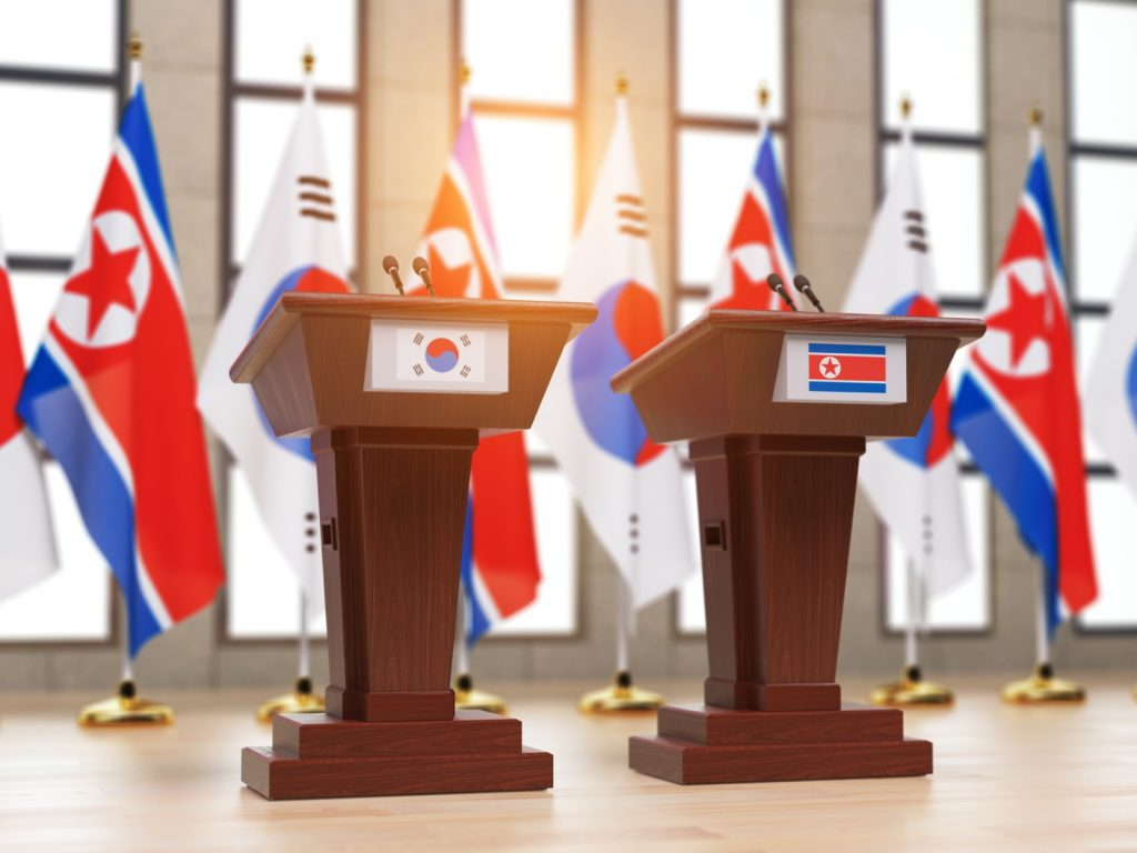 North and South Korean flags and tribunes at international meeting or press conference