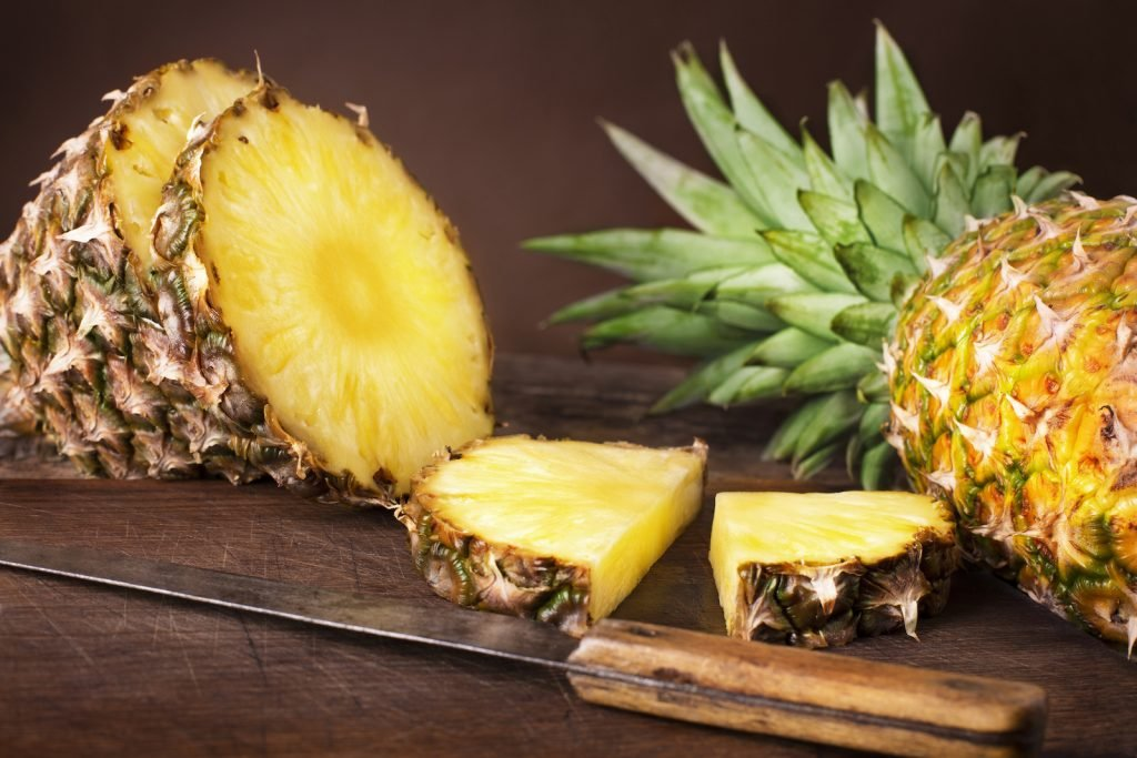 One whole ripe pineappel and one cut in slices lies on a rustik dark brown table