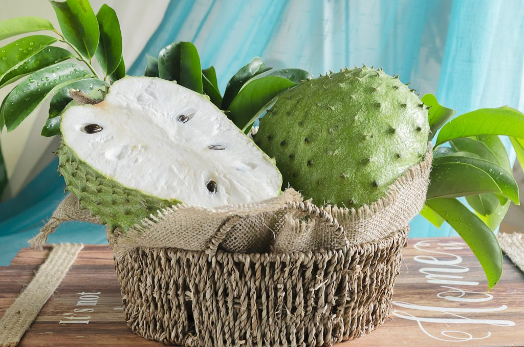 Soursop fruit in a woven basket on a wooden crate with blue background