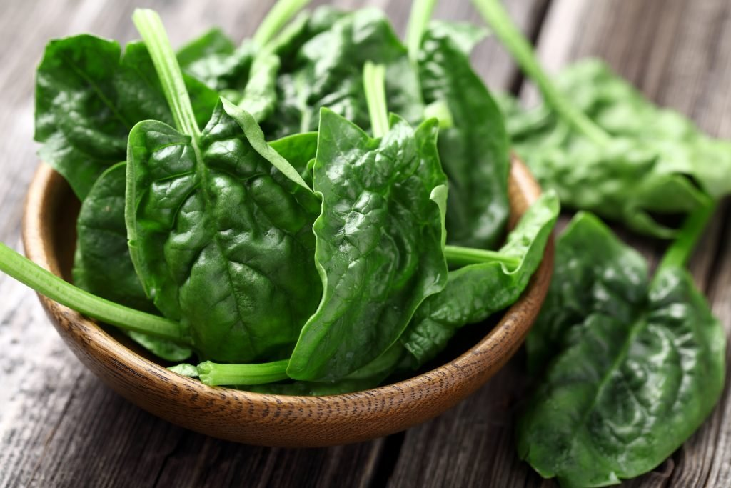 Fresh spinach leaves in a wooden bowl