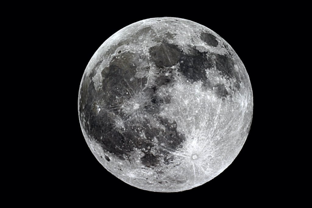 The moon adds beautiful white light to the night sky.