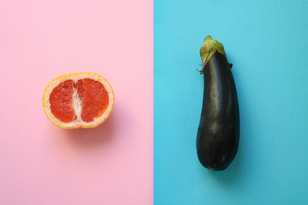 Abstract symbols for male and female gender shown as half a grapefruit and an eggplant on colored backgrounds