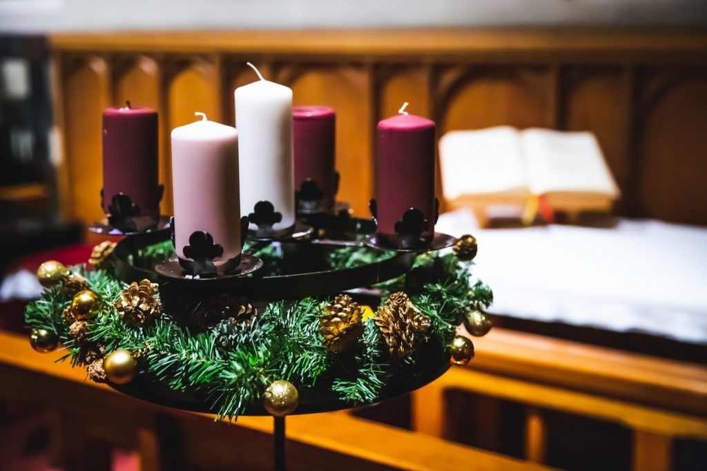 Advent wreath with three purple, one pink, and one white candle