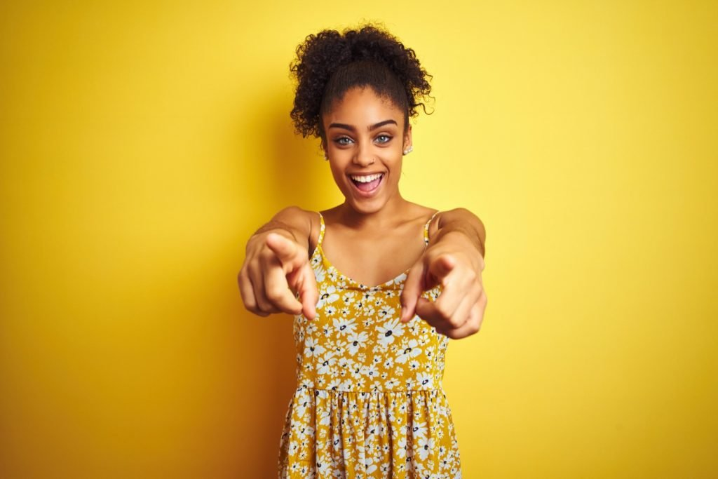 Cheerful African American woman wearing casual floral dress standing over isolated yellow background pointing at the camera smiling