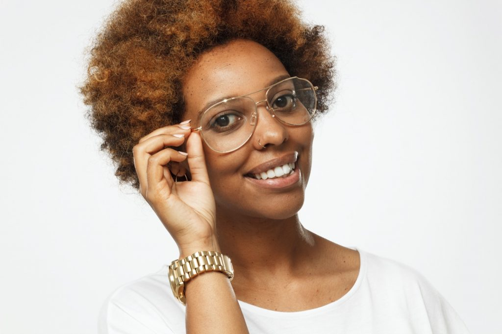 African American woman holding glasses with a gold colored frame