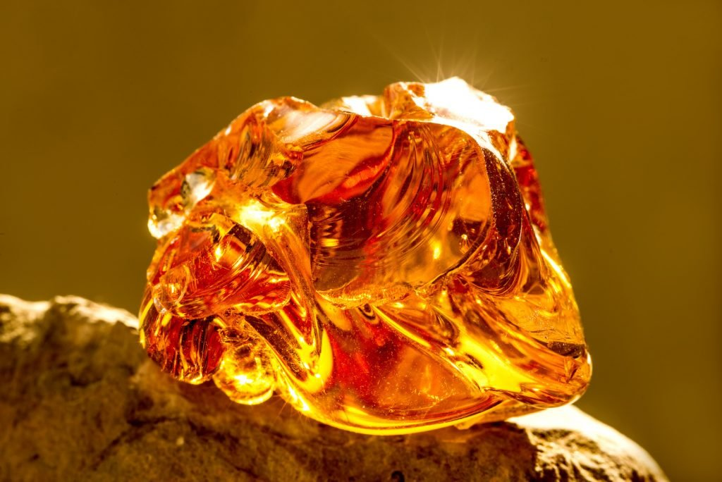 Closeup of uncut amber stone, placed on a grey naturel stone, letting sunlight reflecting in the amber stone