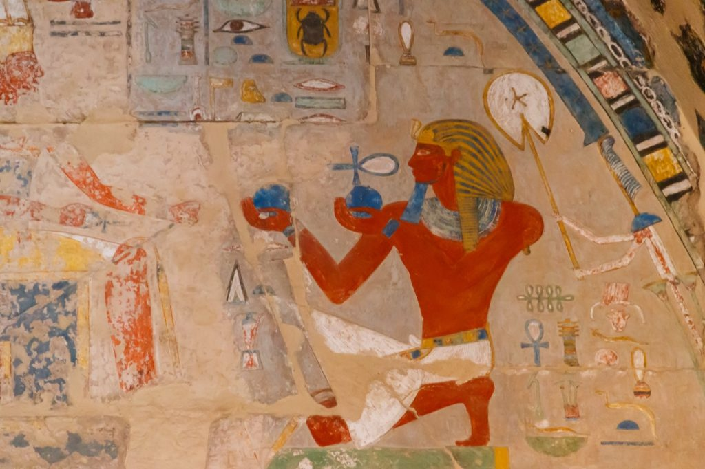 Ancient Egyptian painting with blue and orange colors from the Mortuary Temple of Hatshepsut in Luxor in Egypt