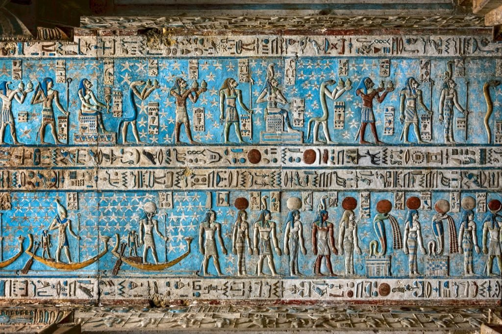 Ancient hieroglyphic carvings on ceiling in Egyptian Blue color