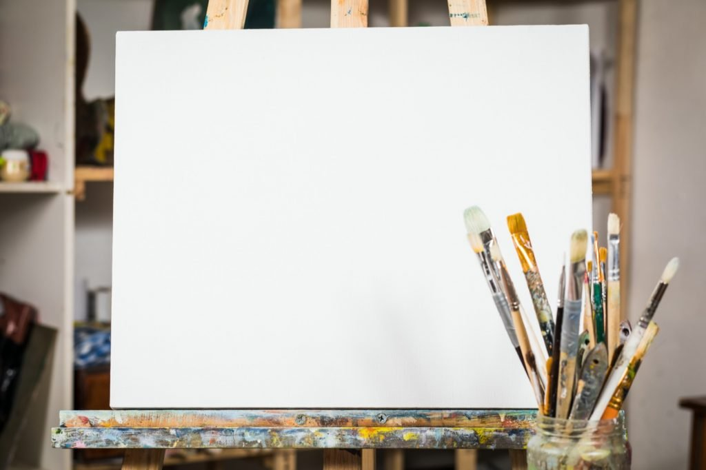 Art equipment for painting. Easel, brushes and blank canvas
