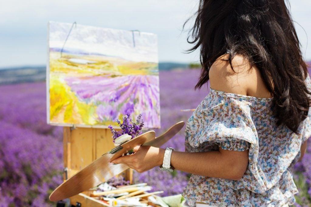 Female artist painting a purple lavender field