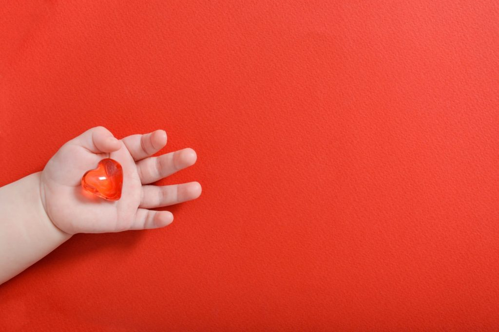 Newborn baby hand on red background holding glass heart