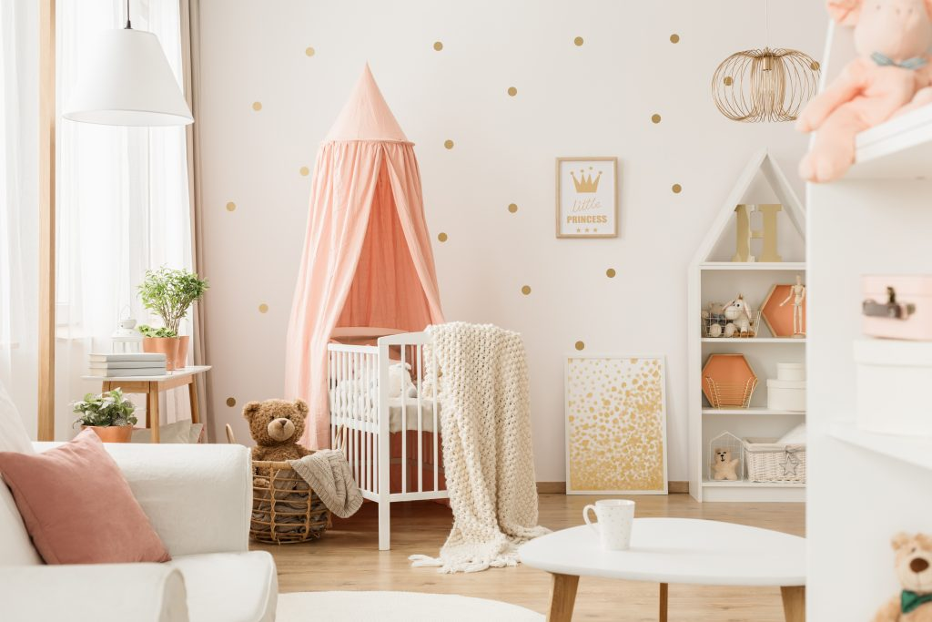 Pink canopy above cradle in baby's bedroom interior with gold posters and teddy bear in basket
