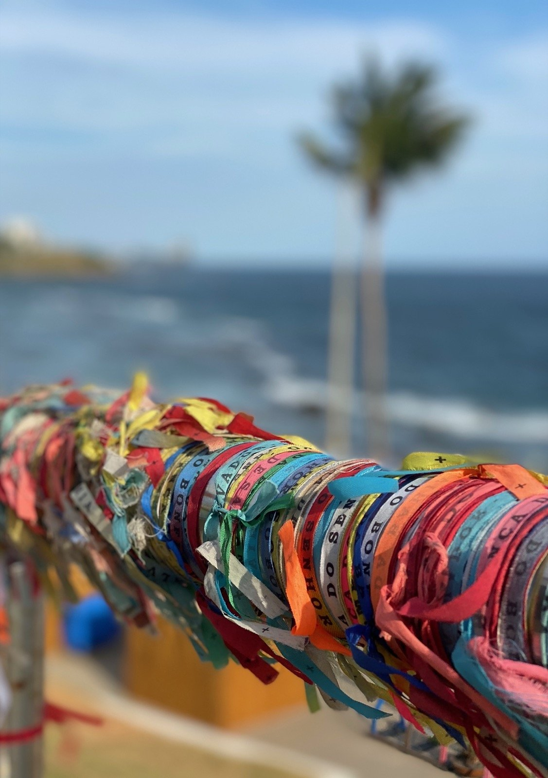 Several Bahia Bands tied around a pole with a blurred coconut tree and the ocean in the background