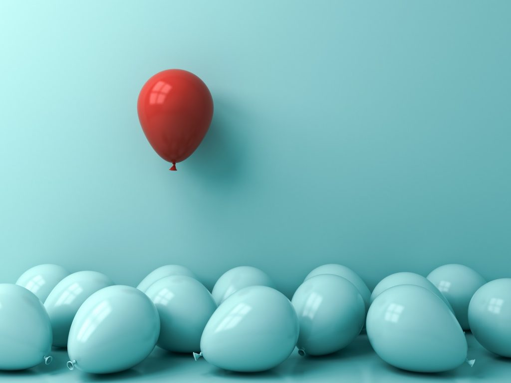 Single balloon in red dominant color stands out from a crowd of balloons in turquoise recessive colors