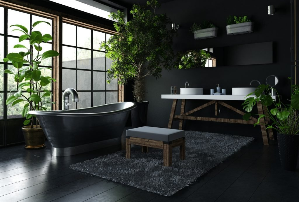 Interior of elegant bathroom in black color with a shiny freestanding metal bath near wide window and lots of green indoor plants around