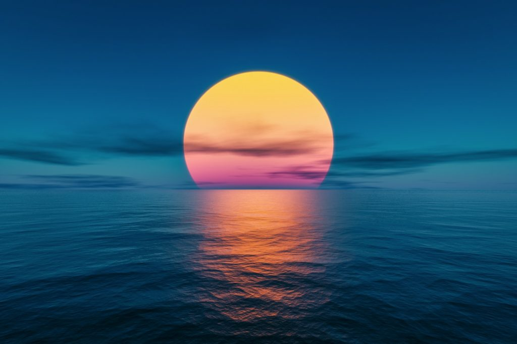 A beautiful colorful sunset over the ocean with yellow and orange sun and dark blue water