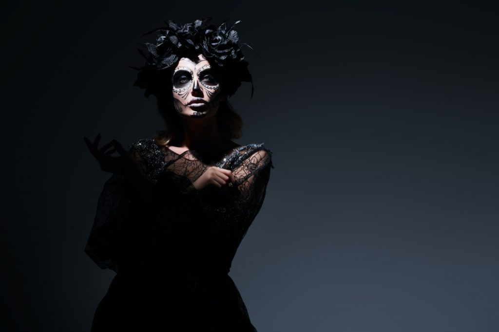Beautiful woman in a dark room wearing black clothes and makeup celebrating Day of the Dead