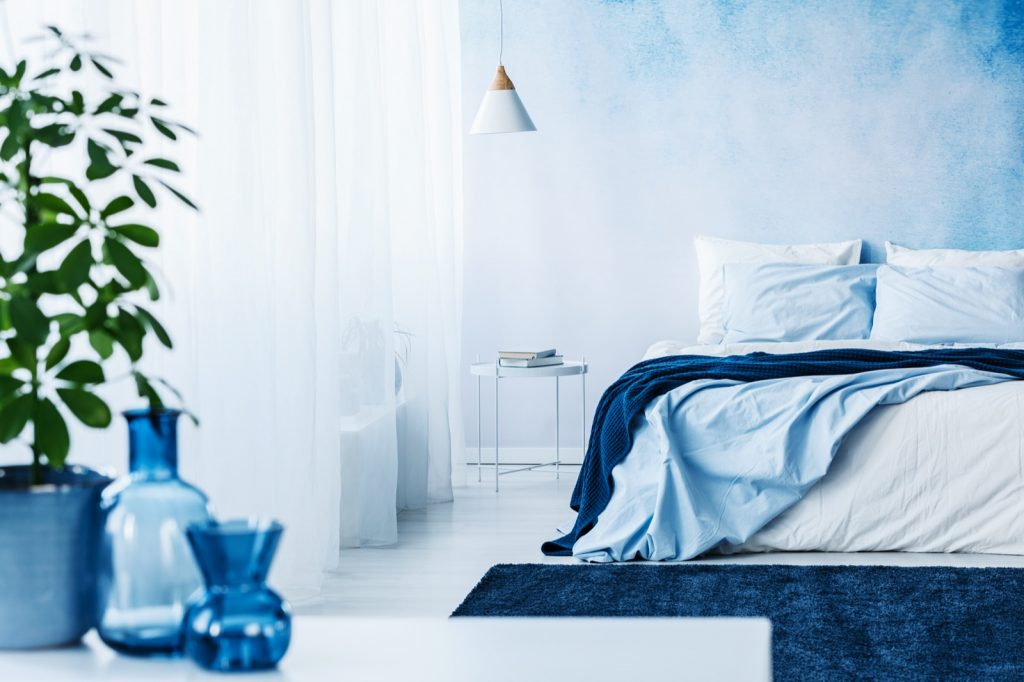 Blue bedroom with vases and a plant in the foreground and a cozy bed with blankets in the background