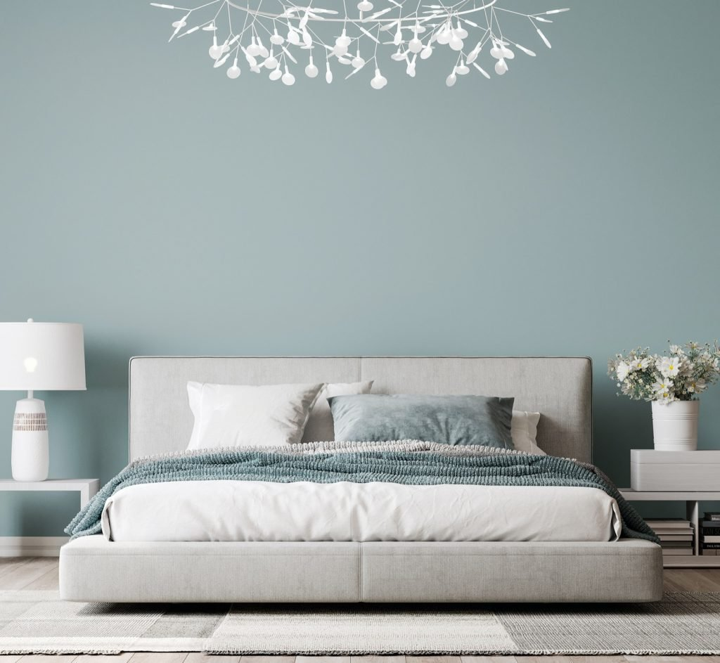 Bedroom interior design with gray bed and elegant home accessories on middle key blue colored wall