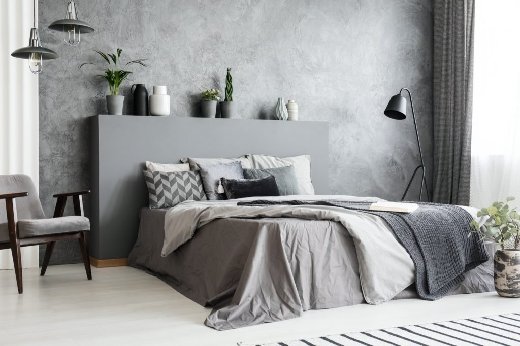 Bedroom interior in monochromatic gray colors with big bed, armchair and lamps against textured wall