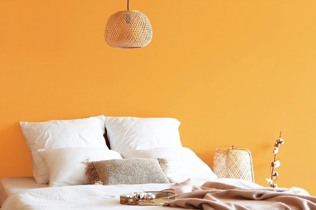 Bedroom with orange wall and white pillows lying on a bed