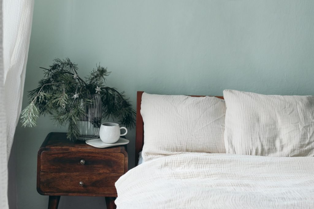 Bedroom with sage green walls and a bed with beige cotton muslin beddings