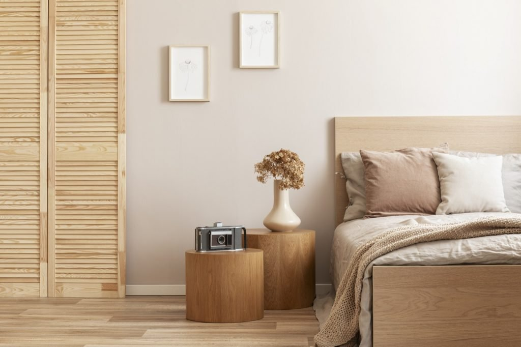 Beige colored bedroom with wooden nightstands and bed