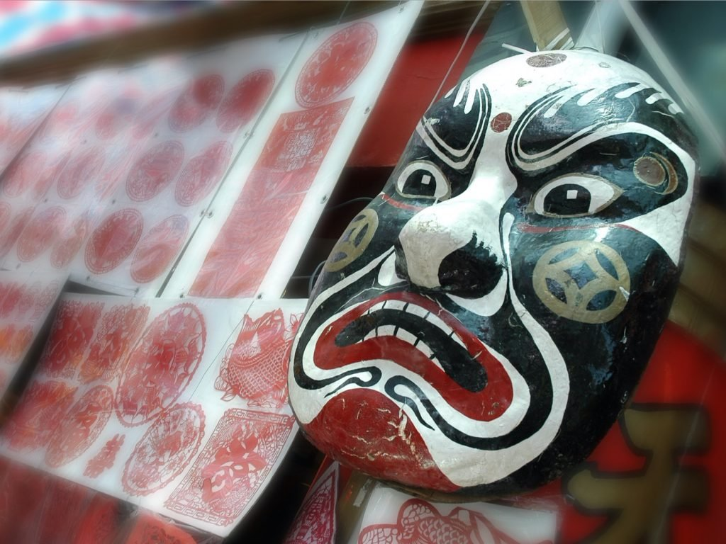 Black Chinese opera mask in focus near stand with different patterns