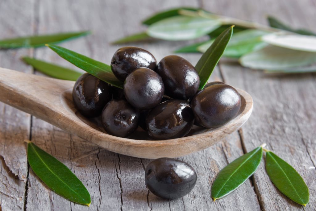 Black olives on a wooden spoon with leaves around